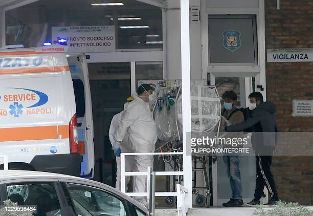 Relatives talk to a patient with COVID-19 as he arrives in an emergency stretcher to the infectious diseases emergency unit at the Cotugno hospital...