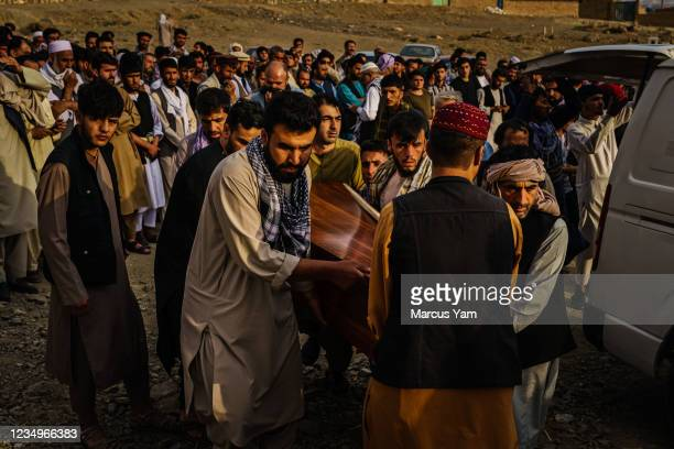 Relatives transport caskets out of a transport vehicle as they attend a mass funeral for members of a family that is said to have been killed in a...