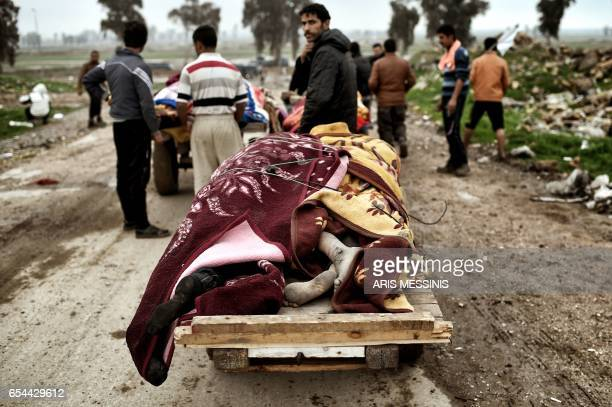 Relatives transport on carts the bodies of Iraqi residents of west Mosul who were killed in an airstrike targeting Islamic State group jihadists in...