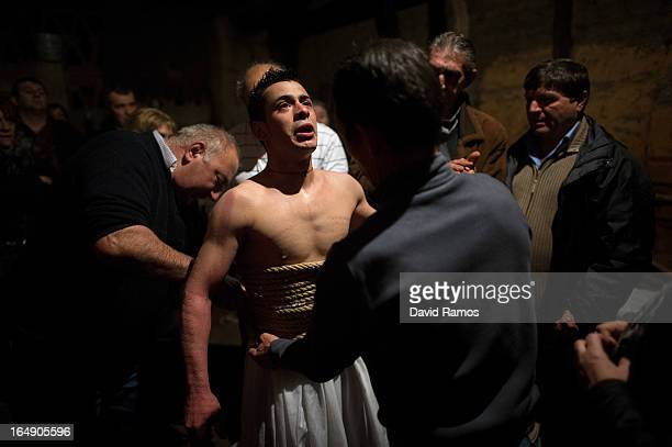 Relatives undress Cesar Higuero Martin aged 25 after walking the way of the cross or 'Via Crucis' at the end of the procession of the 'Empalaos' on...
