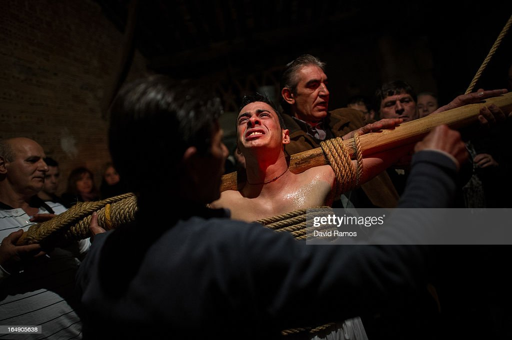 Relatives undress Cesar Higuero Martin, aged 25, after walking the way of the cross or 'Via Crucis' at the end of the procession of the 'Empalaos' on March 29, 2013 in Valverde de la Vera, Spain. Empalaos make the steps of the 'Via Crucis', marking the Stations of the Cross, during the night of Maundy Thursday while bound by rope to a crucifix as an act of penance and to honour a promise made to the Empalaos Brotherhood and the Christ of Vera Cruz, in the town of Valverde de la Vera. The process of dressing the Empalao in the traditional costume is taken with great care, with the family and dressers paying attention to ensure that no harm is caused to the penitent and that they are aided in their recovery, including being massaged and rubbed with rosemary alcohol. Many Spanish towns and villages retain such rites and religious traditions, many passed down from medieval times, across the Easter weekend.