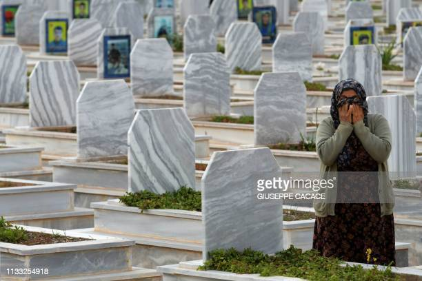 Relatives visit the tombs of Syrian Democratic Forces fighters at a cemetary in the northern Syrian-Kurdish town of Kobane on March 27, 2019.