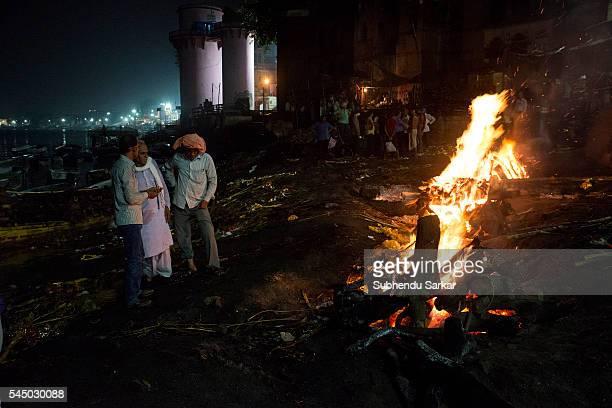Relatives wait as a corpse is being cremated at Manikarnika ghat in Varanasi. It is a traditional holy place on the banks of river Ganges to cremate...