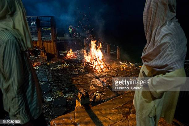 Relatives wait as a corpse is being cremated at Manikarnika ghat in Varanasi It is a traditional holy place on the banks of river Ganges to cremate...