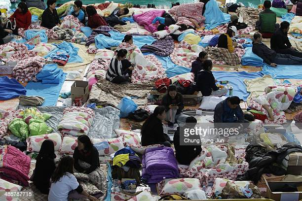 Relatives wait for missing passengers of a sunken ferry at Jindo gymnasium on April 21 2014 in Jindogun South Korea At least sixty four people are...