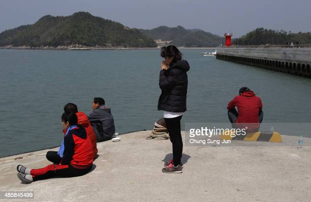 Relatives wait for missing passengers of a sunken ferry at Jindo port on April 21 2014 in Jindogun South Korea At least sixty four people are...