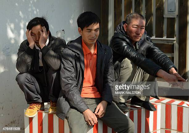 Relatives wait outside a funeral home before being allowed in to identify the body of a family member after the attack at the main train station in...