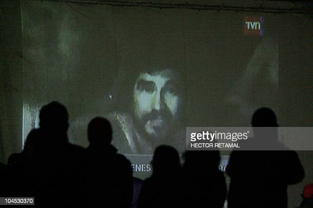 Relatives watch on a large screen a video recorded with a camera in a probe on August 26 2010 of the miners still trapped inside the San Esteban...