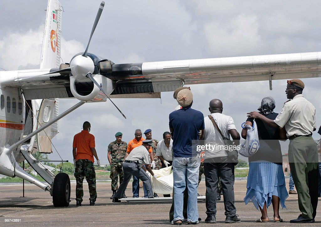 Relatives watch rescue workers as they download the remains of their beloved upon arrival at the Zorg en Hoop airport in Paramaribo on May 17, 2010. Eight people, including pilot and co-pilot, died in a plane crash on May 15 in the hinterlands of Suriname. This is the third accident, second with casualties, with an Antonov airplane of Blue Wing airline in two years in Surinam. AFP PHOTO/Louis ALFAISIE