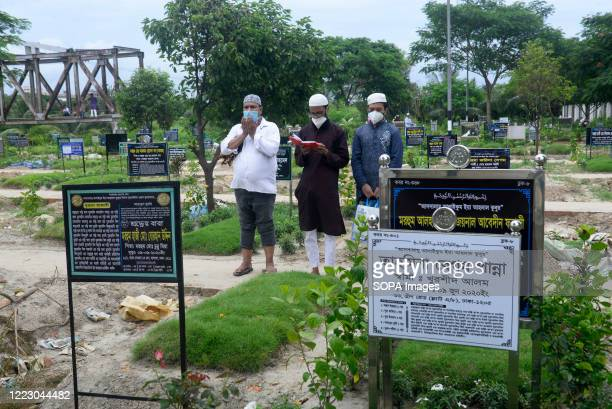 Relatives wearing face masks as a preventive measure pray in front of the tomb of a coronavirus victim. Bangladesh has recorded a total of 130,474...