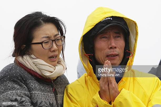 Relatives weep as they wait for missing passengers of a sunken ferry at Jindo port on April 18 2014 in Jindogun South Korea At least twenty five...