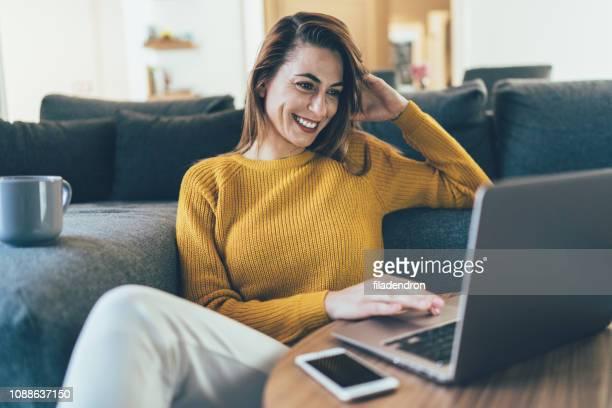家でくつろぐ - 若い女性だけ ストックフォトと画像