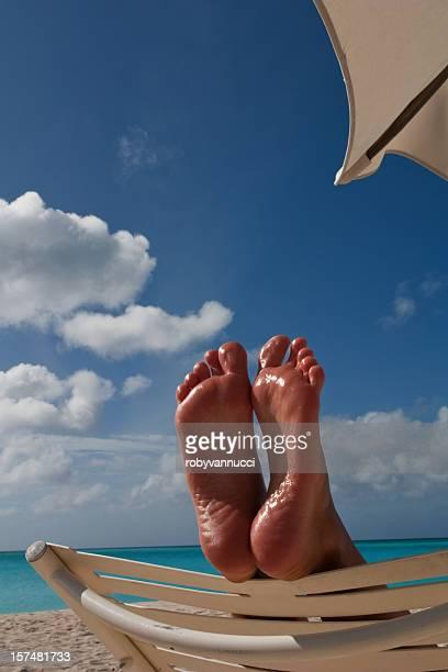 Détendez-vous sur la plage, avec pieds sur une chaise longue