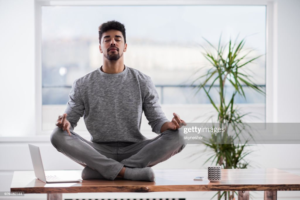 Relaxed African American man exercising Yoga in Lotus position on the table at home. : Stock Photo