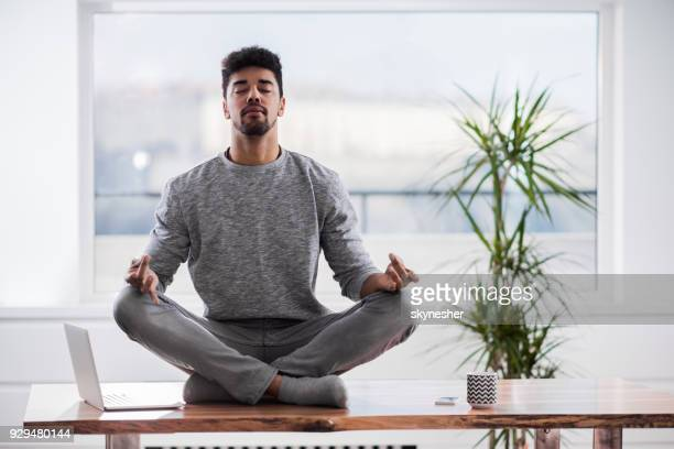 Relaxed African American man exercising Yoga in Lotus position on the table at home.