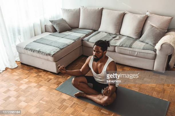 relaxed african american man exercising yoga in lotus position - meditating stock pictures, royalty-free photos & images