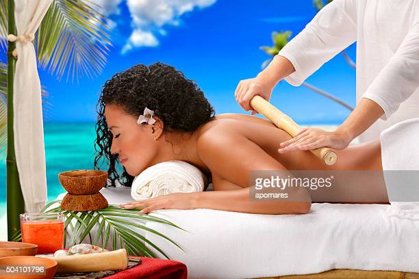 Relaxed African American woman getting bamboo massage therapy beach Spa