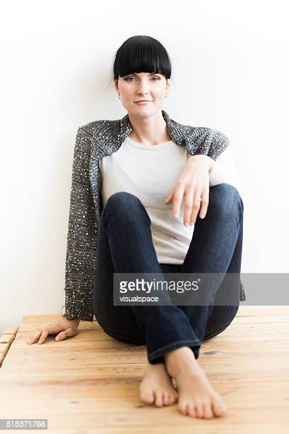 Relaxed and Confident Woman Sitting Relaxed On Wooden Floor