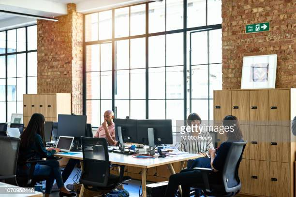 Relaxed and friendly work colleagues in open plan office
