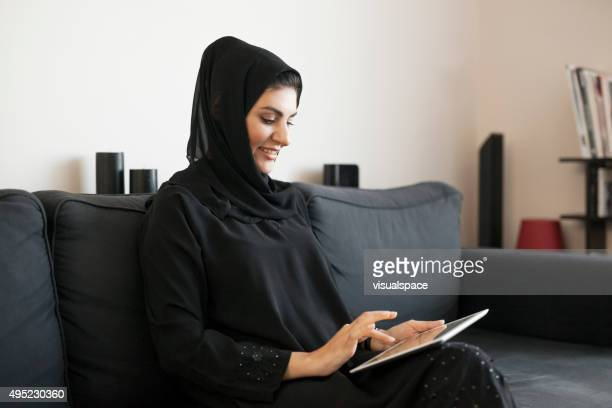 Relaxed Arab Woman Using Digital Tablet at Home