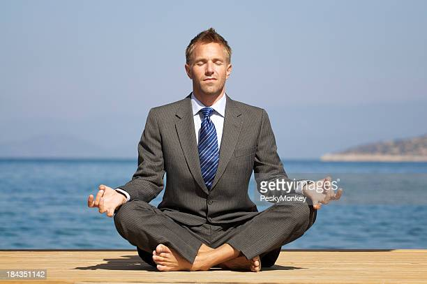 Relaxed Barefoot Businessman Doing Yoga on a Sunny Dock