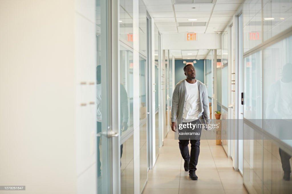 マイアミコワーキングオフィスでのリラックスしたブラックフリーランサーウォーキング : ストックフォト