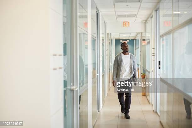 マイアミコワーキングオフィスでのリラックスしたブラックフリーランサーウォーキング - 接近する ストックフォトと画像