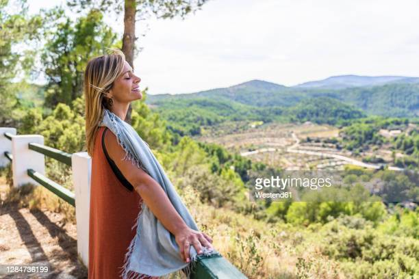 relaxed blond mature woman standing with eyes closed at health retreat - neckwear stock pictures, royalty-free photos & images