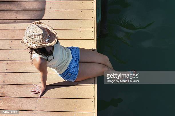 relaxed brunette woman with straw hat sitting on the dock - beautiful long legs stock pictures, royalty-free photos & images