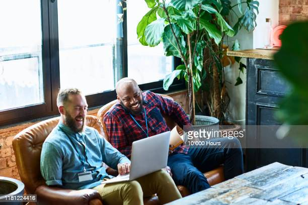 relaxed business partners meeting in office breakout area - persons with disabilities stock pictures, royalty-free photos & images