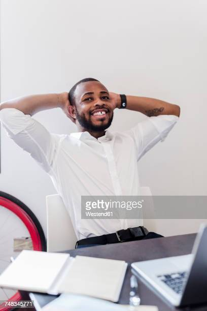Relaxed businessman at desk leaning back