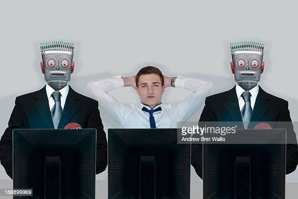 relaxed businessman between stressed robots - robot stock pictures, royalty-free photos & images