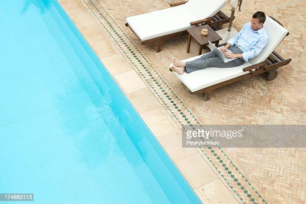 Relaxed Businessman Sitting Poolside Working on Laptop