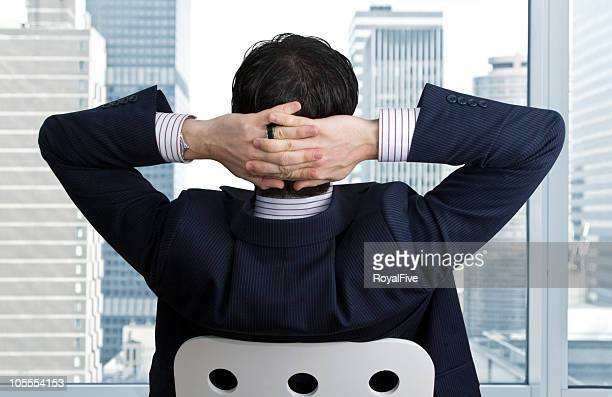 relaxed businessman turns to window with hands behind head - smug stock photos and pictures