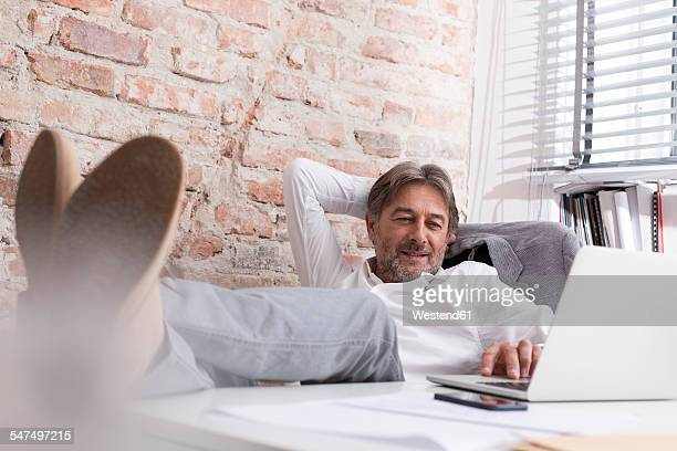 Relaxed businessman using laptop at desk