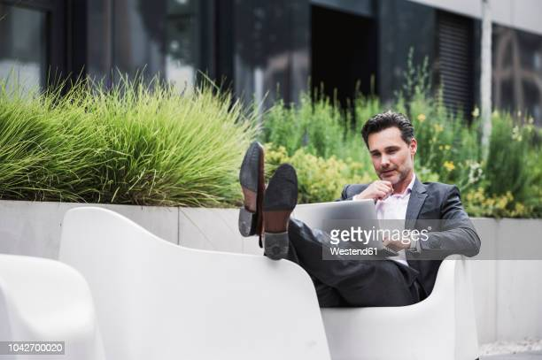 relaxed businessman using laptop outside office building - convenience stock pictures, royalty-free photos & images