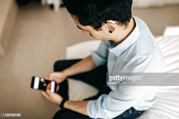 relaxed businessman using phone in hotel room - assistive technology stock pictures, royalty-free photos & images