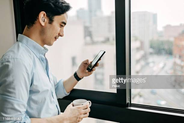 relaxed businessman using phone in hotel room - disabilitycollection stock pictures, royalty-free photos & images