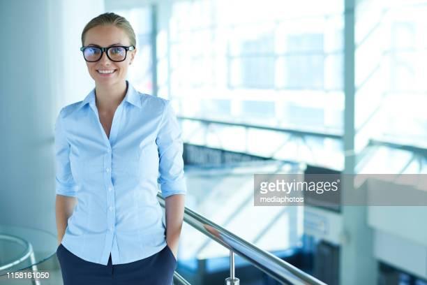 ontspannen zakenvrouw in glazen in kantoor - handen in de zakken stockfoto's en -beelden