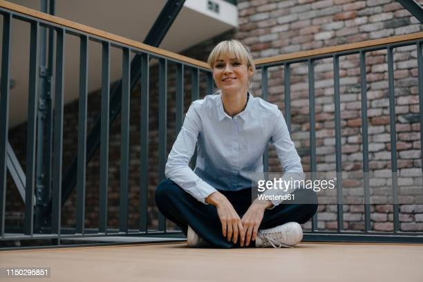 relaxed businesswoman sitting cross-legged on the floor - sitting on ground stock pictures, royalty-free photos & images