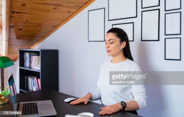 リラックスした落ち着いたビジネスウーマンは、ホームオフィスの職場で目を閉じて休む新鮮な空気の深呼吸をします。オフィスヨガをしたり、目を閉じて瞑想したり。 - 息を止める ストックフォトと画像