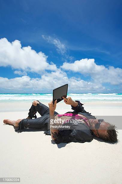 Relaxed Castaway Businessman Using Tablet Computer on Beach