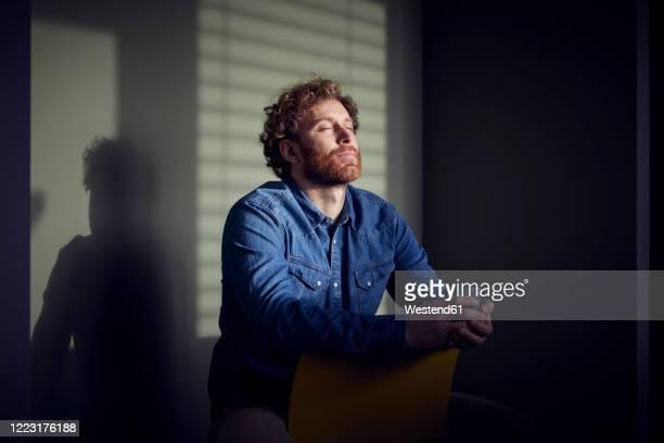relaxed casual businessman sitting down with closed eyes - vergnügen stock-fotos und bilder
