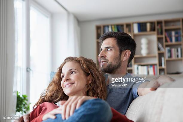 relaxed couple at home on couch - mid volwassen koppel stockfoto's en -beelden
