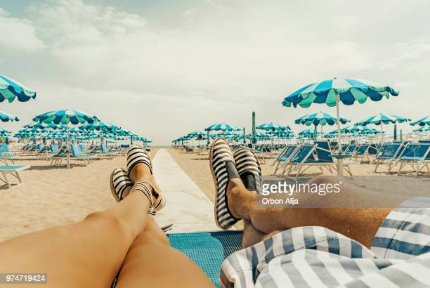 relaxed couple at the beach - espadrilles foto e immagini stock