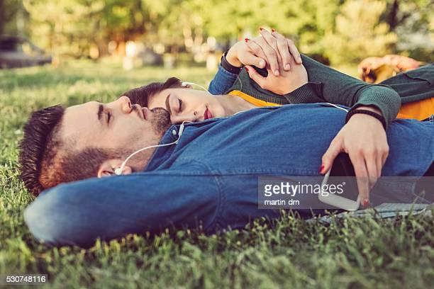 の音楽を楽しみながらリラックスしたカップル公園の