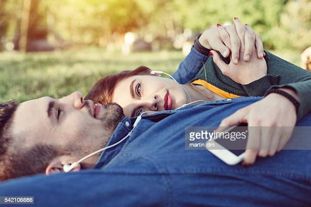 relaxed couple enjoying the music in the park - love at first sight stock pictures, royalty-free photos & images