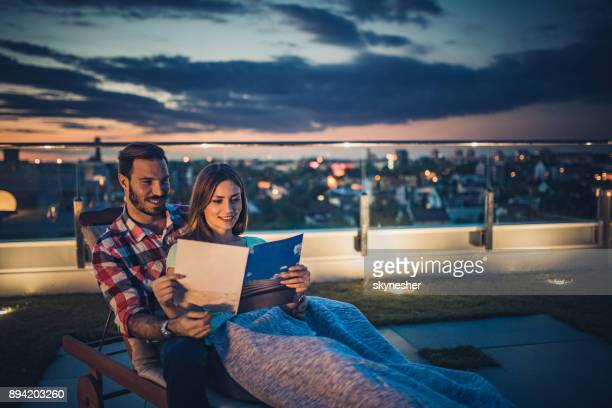 relaxed couple reading a magazine on deck chair at penthouse terrace. - penthouse magazine photos stock pictures, royalty-free photos & images