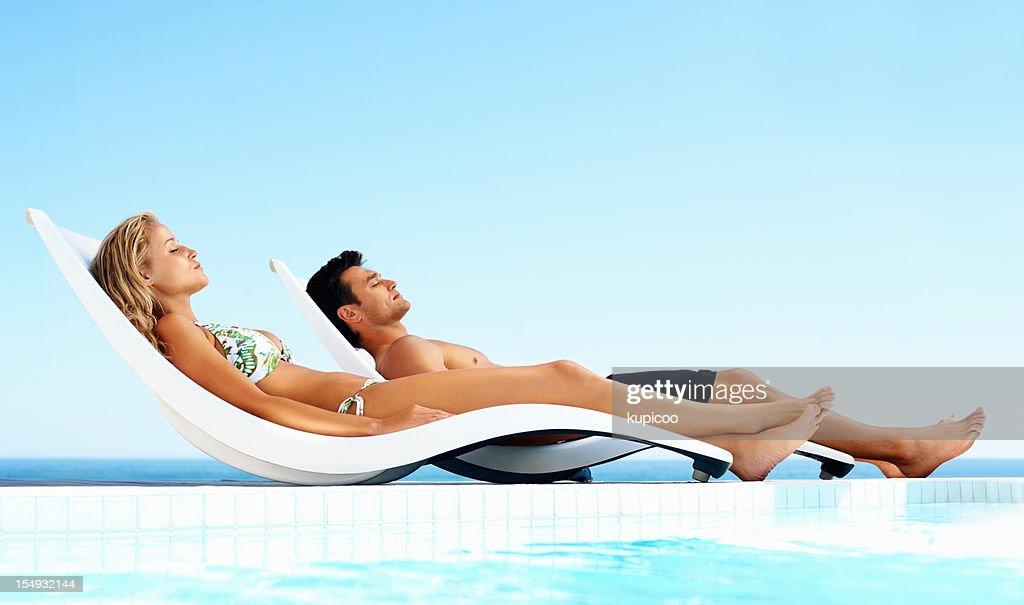 Coppia rilassata prendendo il sole in piscina : Foto stock