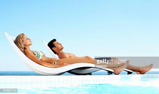 Détendue couple prendre un bain de soleil au bord de la piscine